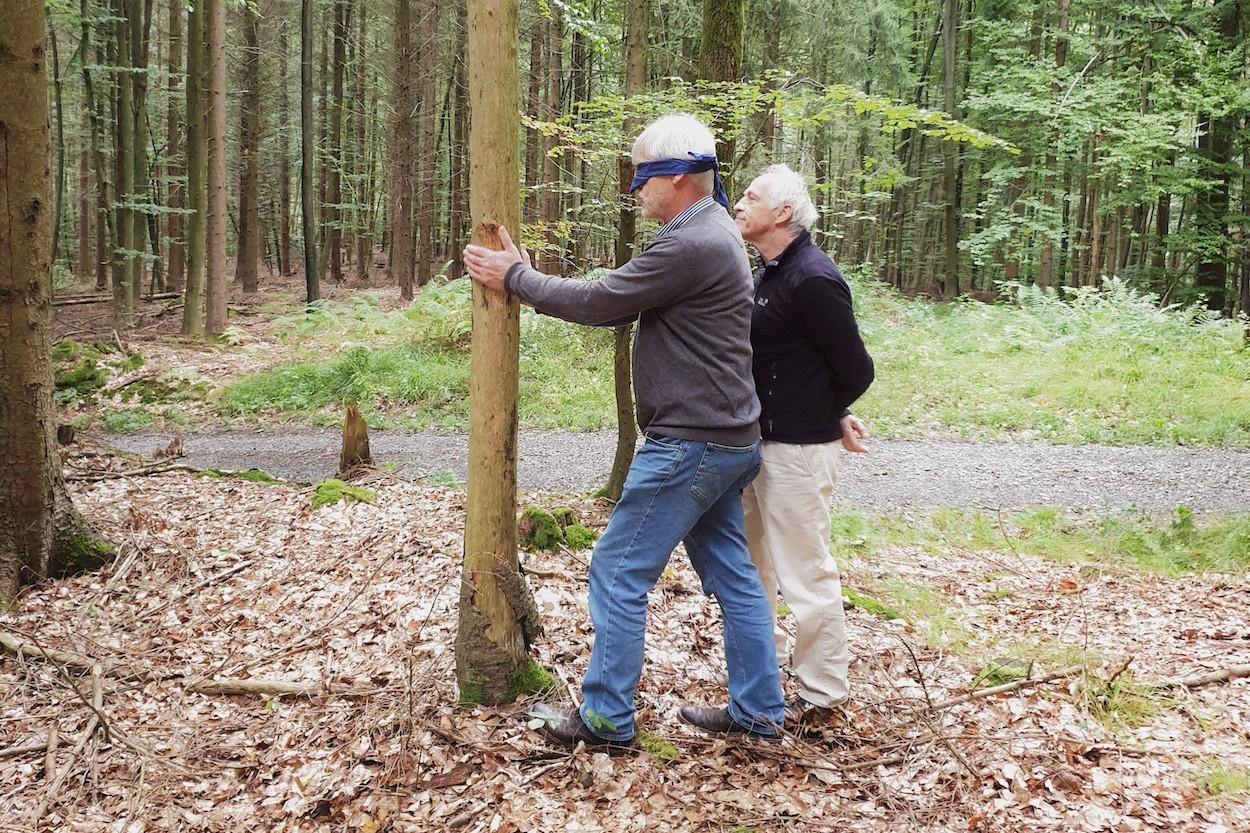 Ein Mann betastet mit verbundenen Augen einen Baumstamm, sein Begleiter beobachtet ihn dabei