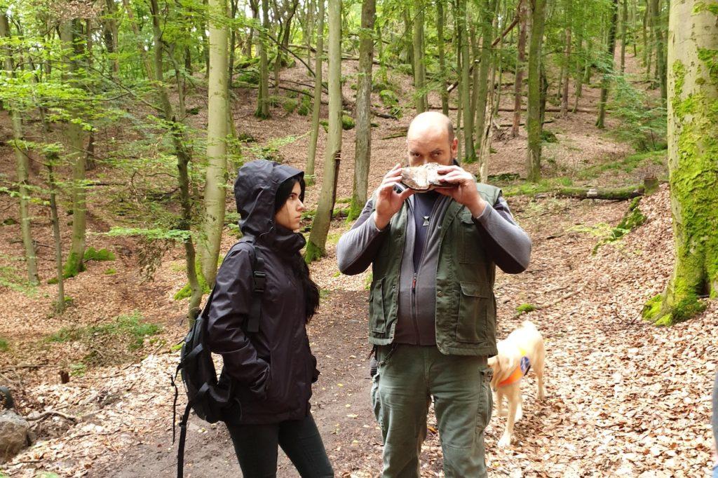 Eine Frau und ein Mann stehen im Wald. Der Mann riecht an einem Baumpilz, die Frau beobachtet ihn.